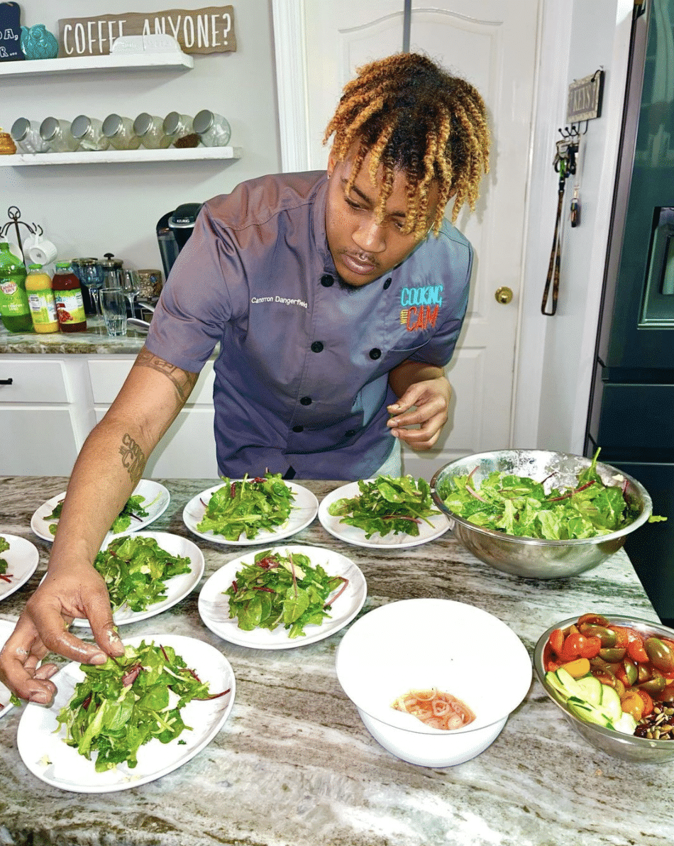 Chef Camerron Dangerfield preparing plates of food in a kitchen.