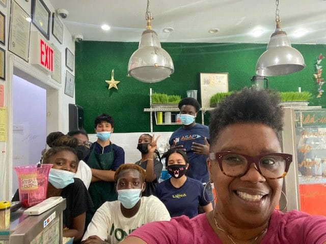 The owner of the Nourish Spot with a group of interns/young people from the community.