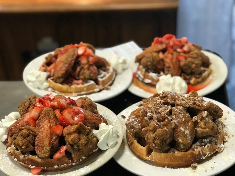 Four plates of chicken and waffles with fruit toppings.