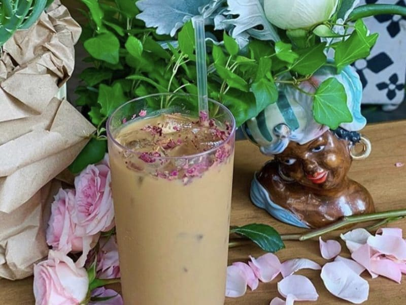 Rose petals surrounding a cup of cold brew